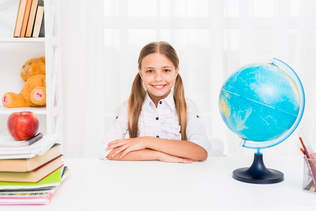 Diligent schoolgirl sitting at table next to globe in classroom