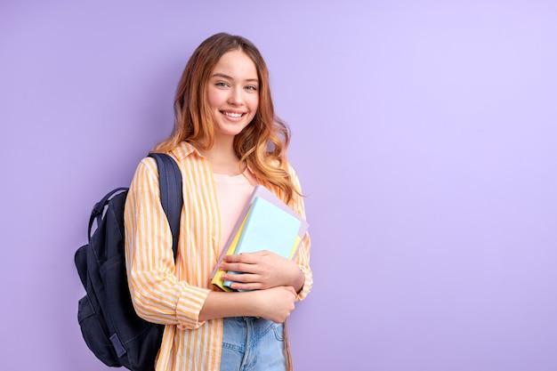 バイオレットでポーズをとるランドセルと本を運ぶ勤勉な恥ずかしがり屋の白人学生の女の子