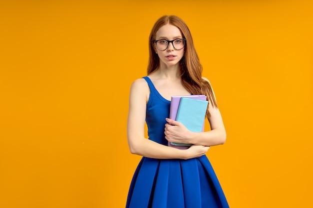 手に本を持って立っている眼鏡の勤勉な学生または教師、自信を持ってカメラを見て、ポーズをとっている眼鏡の教育を受けた賢い女性