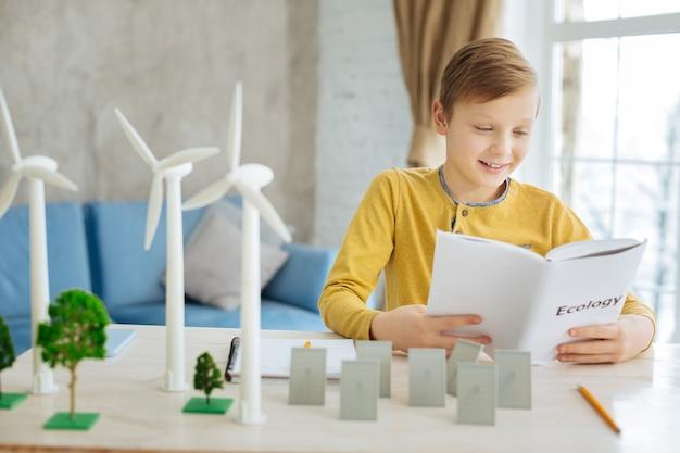 Прилежный ученик. приятный малолетний мальчик сидит за столом с моделями альтернативных источников энергии и читает соответствующий раздел в своей книге по экологии.