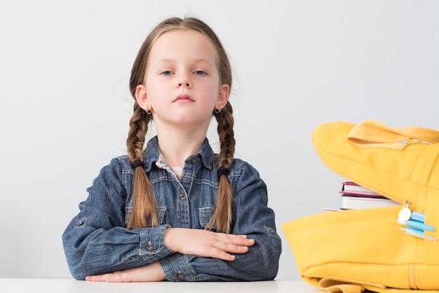 Прилежный ученик. серьезная школьница, сидящая за столом с желтым рюкзаком