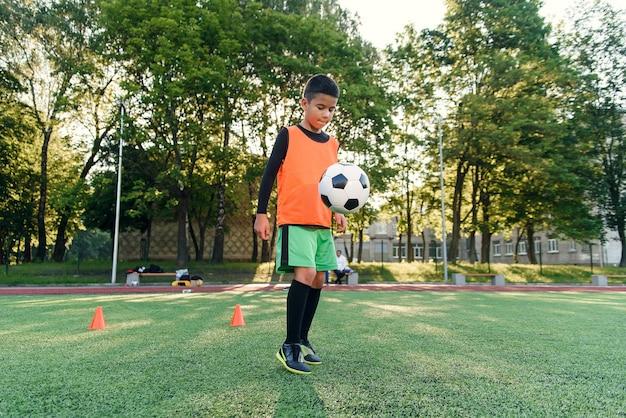Прилежный подросток-футболист набивает футбольный мяч на ногах ботинками