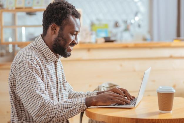 Добросовестный работник. приятный жизнерадостный молодой человек сидит за столом в кафе и печатает на клавиатуре ноутбука, широко улыбаясь