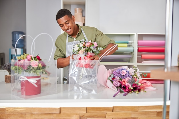 Diligent worker with a rose bunch in a pot placing them in a clear bag lying on a counter