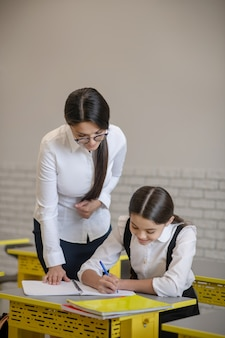 Diligently writing girl and observing nearby attentive teacher in classroom during lesson