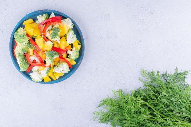 Fascio di aneto accanto a un piatto di insalata su sfondo marmo. foto di alta qualità
