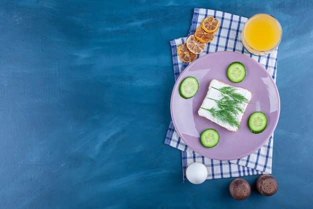 Dill on a cheese bread next to sliced cucumber on a plate next to materials on a tea towel , on the blue.