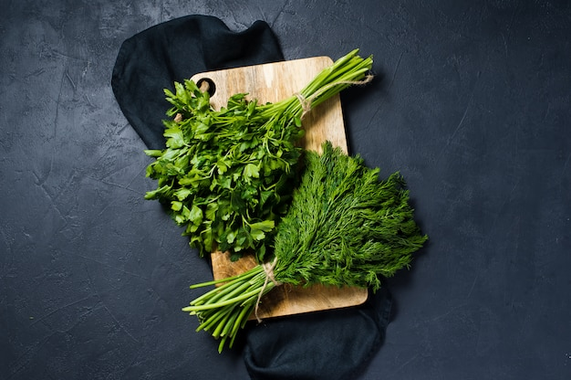 Dill and parsley on a wooden chopping board.