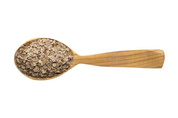 食品に追加するためのディルシード。白で隔離される木のスプーンでスパイスします。