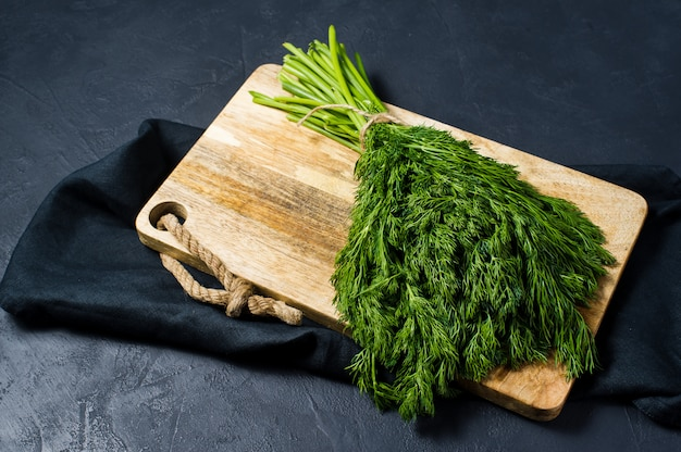 Dill on a wooden chopping board.