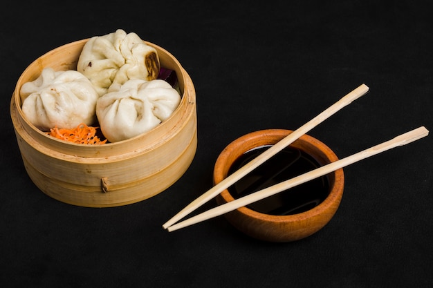 Dim sum along with carrot salad served in small steamer basket and soya sauce bowl with chopsticks on black background