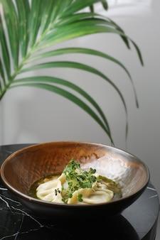 대리석 테이블에 세라믹 접시 근접 촬영에 딤섬. 마이크로 그린과 함께 제공되는 딤섬 중국 전통 음식