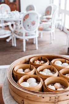 Dim sum set in steamer baskets with dinning room in background.