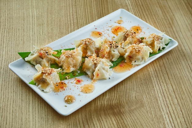 Dim sum with chicken, pork or seafood on a white ceramic plate with sweet and sour sauce on wooden surface