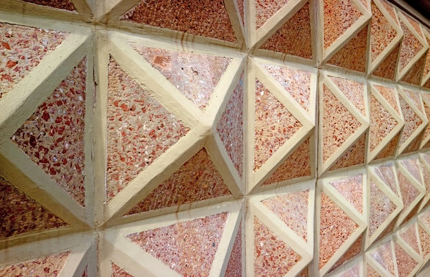 Diminishing perspective of a 3d geometric patterned concrete with red stones wall