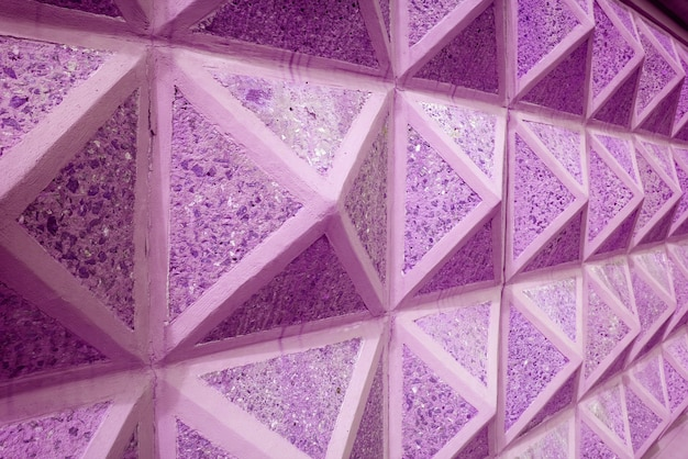 Diminishing perspective of purple pink colored geometric 3d concrete wall for abstract background