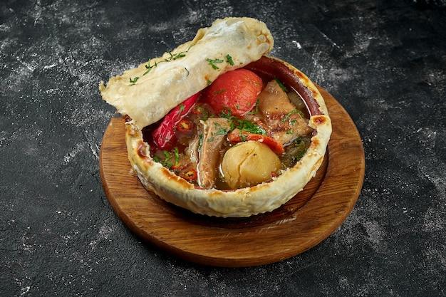 Димлама - тушеное мясо с различными сочетаниями мяса (говядины или баранины), картофеля, лука, овощей на темном столе