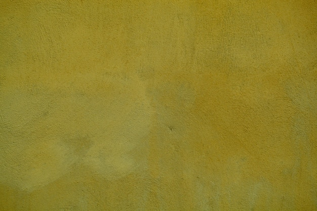 Dingy dark ochre painted wall  texture for vintage or retro themes in a full frame view.