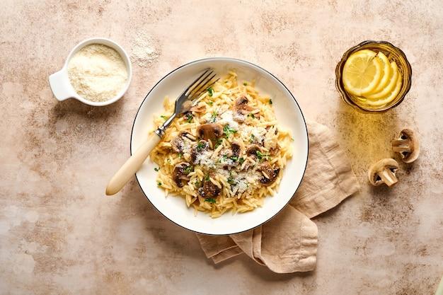 イタリアのパスタリゾーニ、マッシュルーム、ソース、パルメザンチーズ、タイム、ニンニク、オリーブオイル、スレート上の白いプレートでの食事