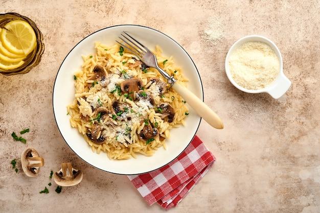 イタリアのパスタリゾーニ、マッシュルーム、ソース、パルメザンチーズ、タイム、ニンニク、オリーブオイル、白いプレートでの食事