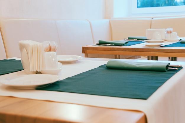 Столовая с пустыми белыми тарелками, серебряными столовыми приборами и зелеными салфетками, служащими для еды