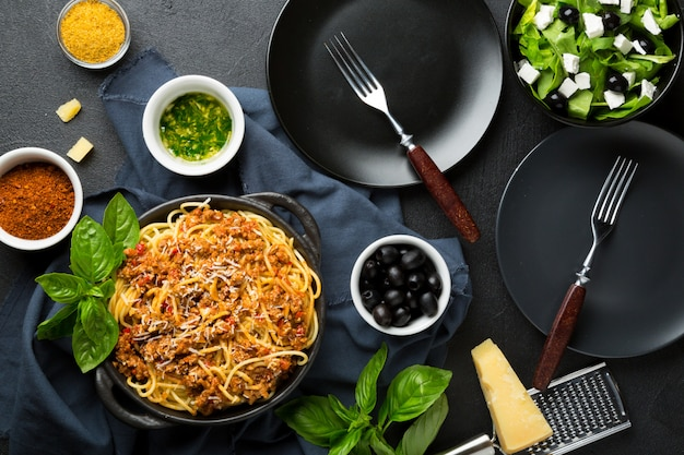 Dining table concept. spaghetti with bolognese sauce, vegetable and greens salad with olives, parmesan cheese, spices and empty plates