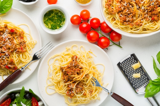 Dining table concept. spaghetti with bolognese sauce, vegetable and greens salad with olives, parmesan cheese and spices