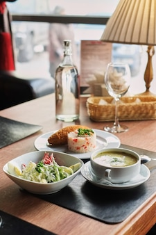 Dining table: a plate of soup, risotto with cutlet and vegetable salad side view