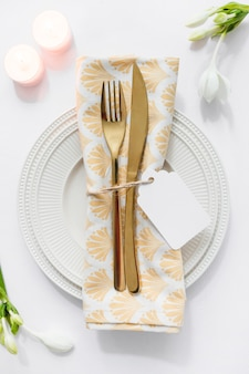 Dining table setting with folded napkin and candles on white background