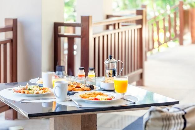 食べ物のプレートとダイニングテーブル。高級ホテルでの2人分の美味しい朝食。ガラスとコーヒーカップにオレンジジュースを入れた、食べ物でいっぱいのプレートを備えたホテルの朝食用テーブル