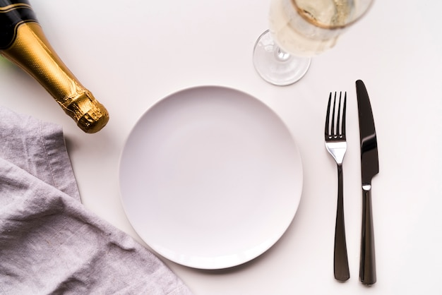 Dining table with empty plate and champagne bottle over white background