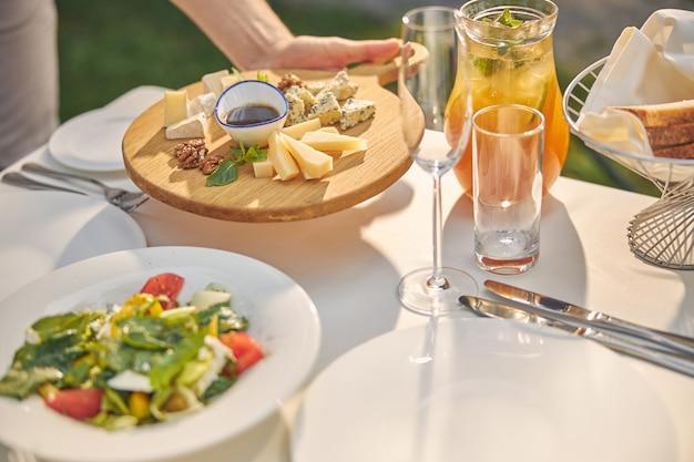 Обеденный стол с апельсиновым лимонадом и вкусной вкусной едой для высоких гостей