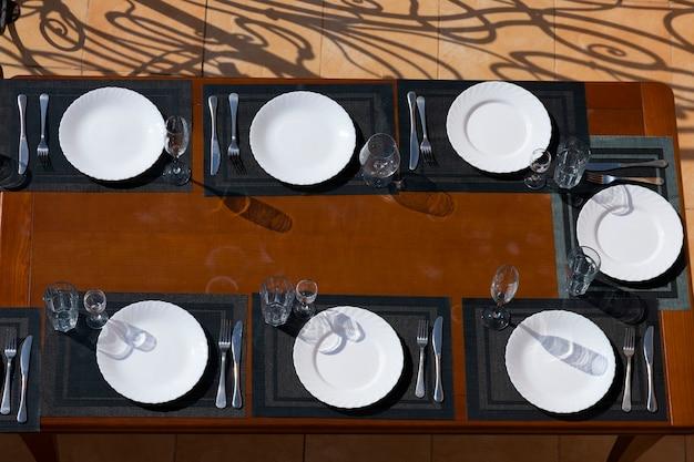 皿、グラス、フォーク、ナイフを備えたダイニングテーブル。食べ物なし。上からの眺め。