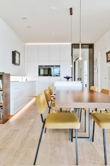Dining zone with table and chairs and hanging lamps in modern light minimalist apartment with open concept kitchen