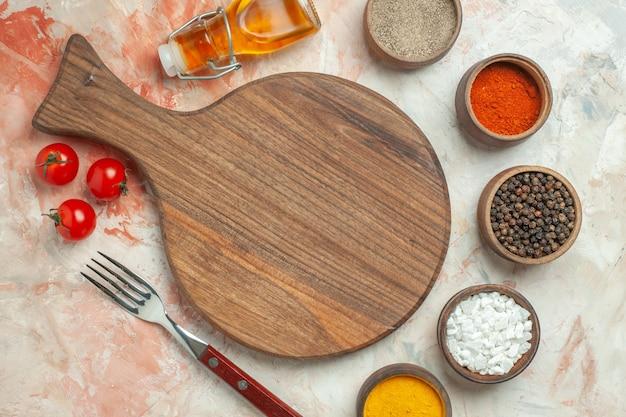 木製のまな板の白いプレートにトマトと混合色の背景にさまざまなスパイスの落ちたオイルボトルをナイフで夕食の背景
