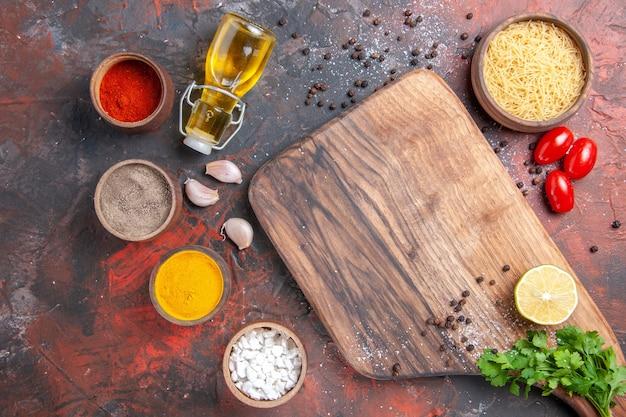 未調理のパスタまな板レモンと緑のトマトの束と暗いテーブルの上のさまざまなスパイスと夕食の背景