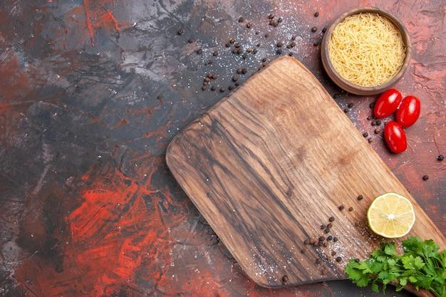 Sfondo cena con tagliere di pasta cruda limone un mucchio di pomodori verdi pepe sul tavolo scuro