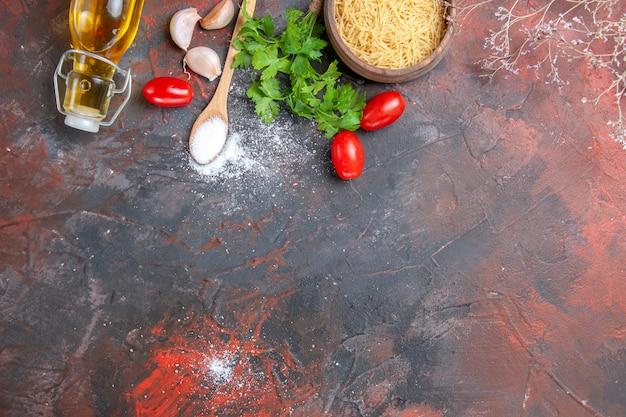 요리하지 않은 파스타가 있는 저녁 식사 배경은 병 마늘 토마토 채소와 검은색 배경에 다른 제품을 떨어뜨렸습니다.