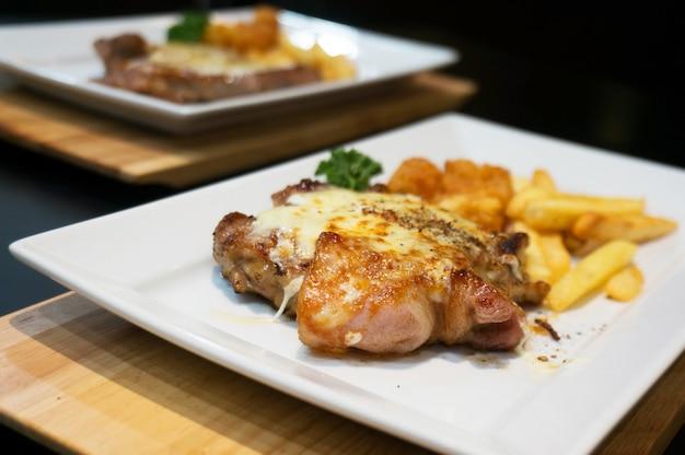 Ужин, стейк из курицы, картофель фри и соус.