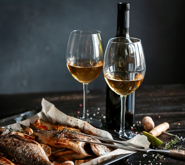 Dinner concept with two glasses of white wine, baked fish
