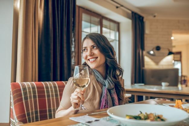 공식 만찬. 레스토랑의 테이블에 앉아 행복해 보이는 검은 머리의 귀여운 여성