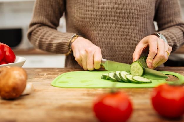 自分のための夕食。正確な女性がキッチンに滞在し、プラスチックの机の上でサラダの材料を切り刻む
