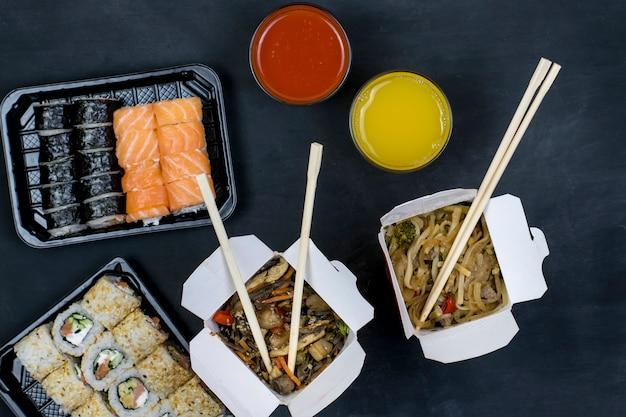 2 인 저녁. 일본 음식 배달. 검은 배경에 야채와 함께 초밥과 뜨거운 국수