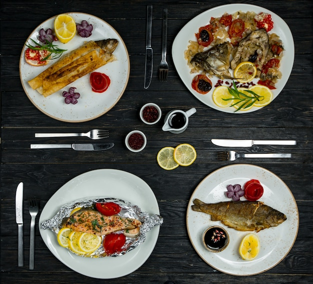 Dinner menu set for 4 pax, different fish , seafood meals in white plates with cutlery and sauces