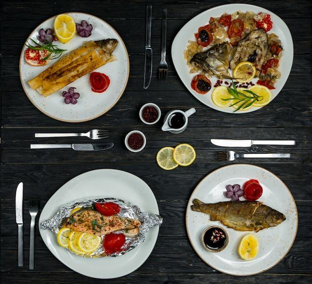 Меню ужина на 4 персоны, разная рыба, морепродукты в белых тарелках со столовыми приборами и соусами