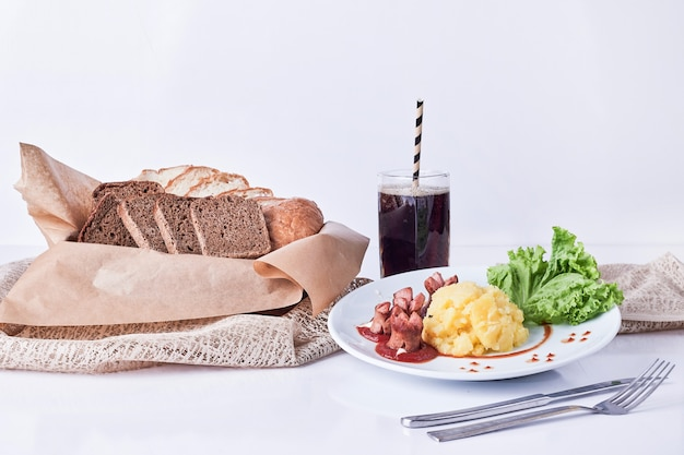 Ужин с ломтиками хлеба и стаканом напитка.