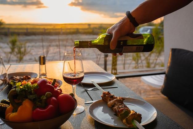 일몰과 와인이 있는 테라스에서 저녁 식사 테라스에서 고기 축하를 위한 야외 테이블여름철 일몰 음식여름 거리에서 친구를 위한 테이블이 있는 아름다운 일몰