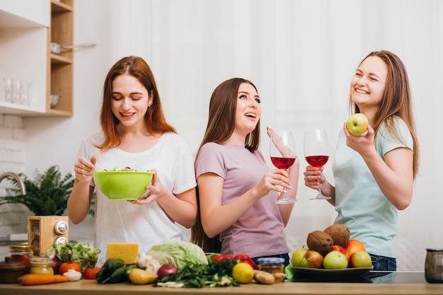 ディナーパーティー。一緒に素晴らしい時間を。友情の楽しみ。赤ワイングラスを飲み、健康的な食品を食べる笑顔の女性。