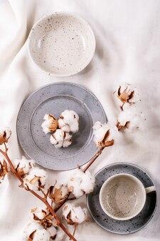 저녁 식사 장소 설정. 흰색 섬유 표면에 목화 꽃으로 장식 된 파란색 현대 세라믹 접시. 평면도, 평면 누워.