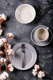 저녁 식사 장소 설정. 어두운 질감 표면에 목화 꽃으로 장식 된 실버 포크가있는 파란색 현대 세라믹 플레이트. 평면도, 평면 누워.